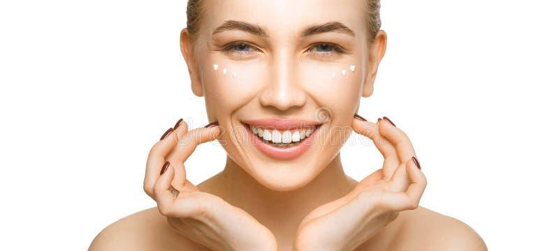 Vrouw wat betreft haar gezicht door handen Het toepassen van room op een perfecte vlotte zachte huid royalty-vrije stock afbeelding