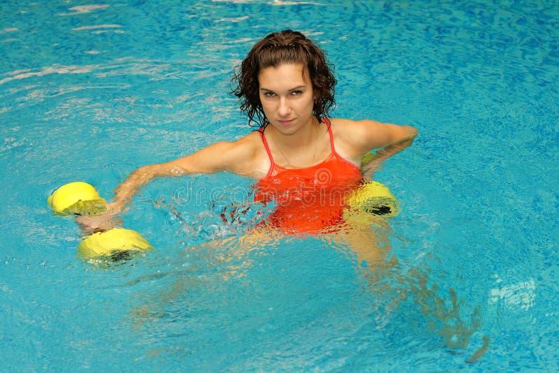 Vrouw in water met dumbbels royalty-vrije stock afbeeldingen