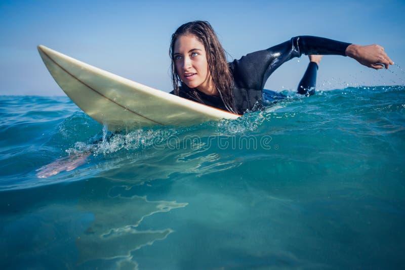 vrouw in wetsuit met een surfplank op een zonnige dag stock afbeeldingen