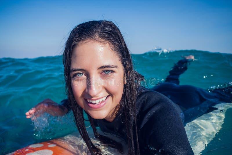 vrouw in wetsuit met een surfplank op een zonnige dag royalty-vrije stock foto's
