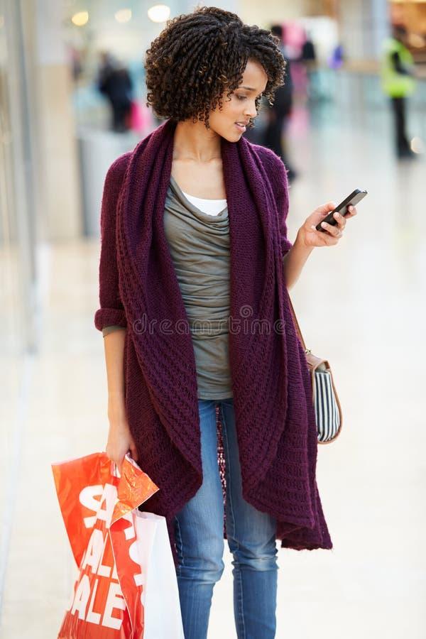 Vrouw in Winkelcomplex die Mobiele Telefoon met behulp van royalty-vrije stock afbeelding