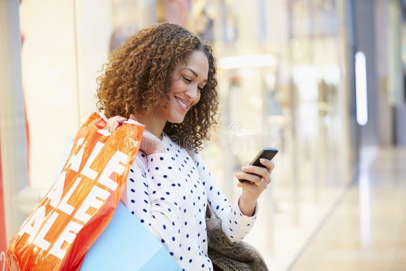 Vrouw in Winkelcomplex die Mobiele Telefoon met behulp van stock foto