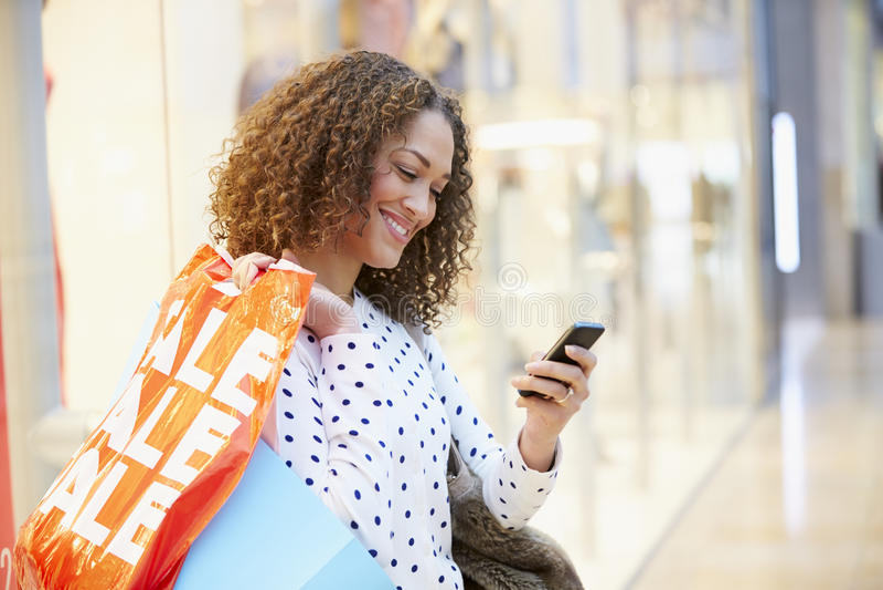 Vrouw in Winkelcomplex die Mobiele Telefoon met behulp van stock afbeelding