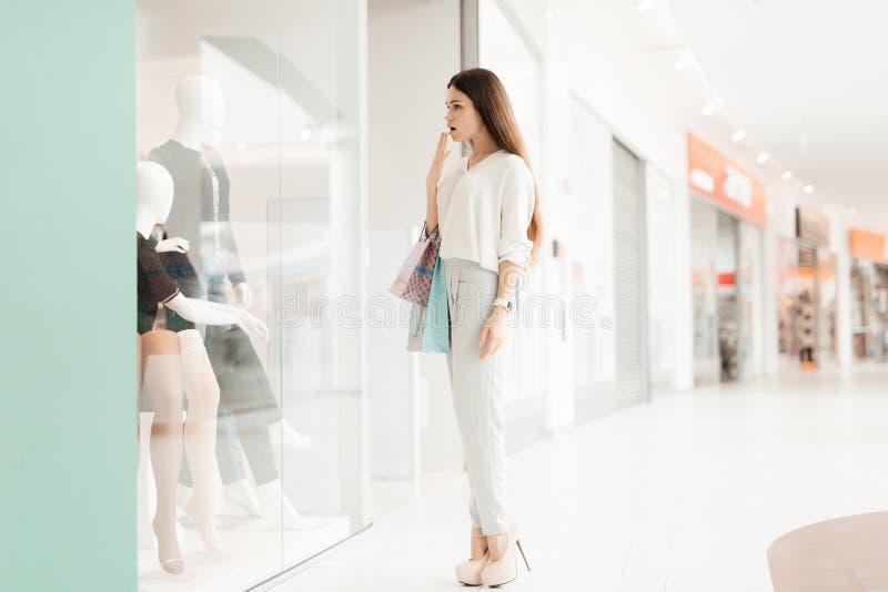 Vrouw in winkelcomplex Het meisje bevindt zich dichtbij opslagvenster bekijkend nieuwe kleding royalty-vrije stock foto