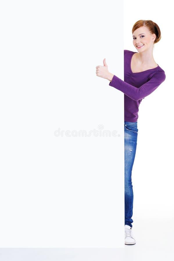 Vrouw withthumbs-op dichtbijgelegen leeg aanplakbord royalty-vrije stock foto