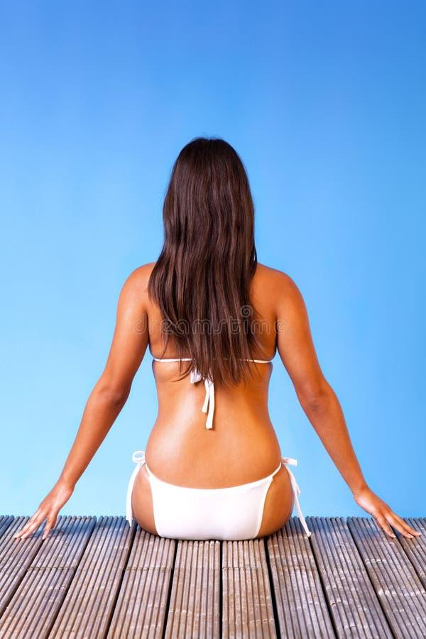 Vrouw in witte bikini die aan het eind van een pijler wordt gezeten stock fotografie
