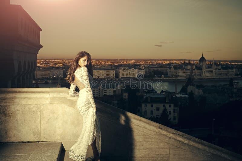 Vrouw in witte huwelijkskleding op de mening van de avondstad, manier Sensuele vrouw met lang haar op balkon, schoonheid Bruid me royalty-vrije stock afbeelding