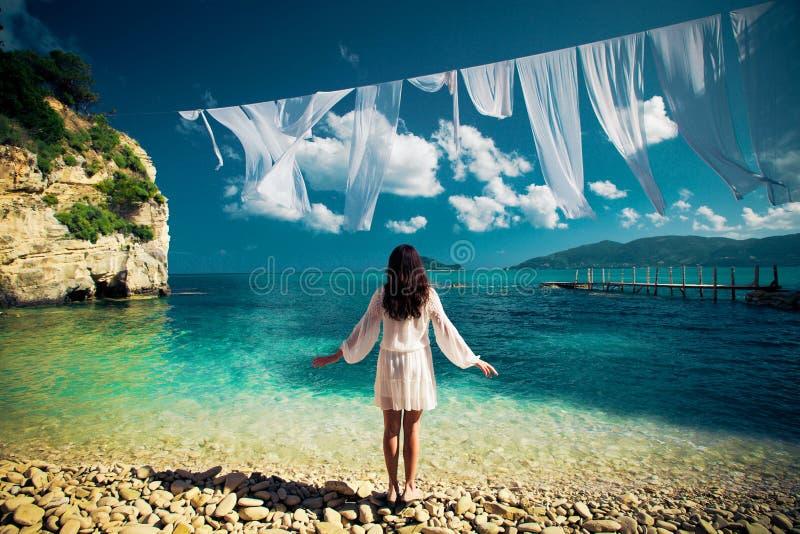 Vrouw in witte kleding die zich op strand bevinden stock afbeelding
