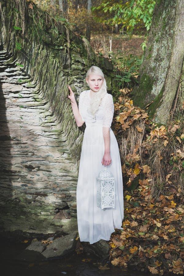 Vrouw in witte kleding en lantaarn bij een brug stock foto