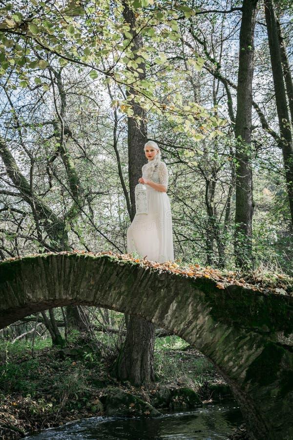Vrouw in witte kleding op een steenbrug royalty-vrije stock fotografie