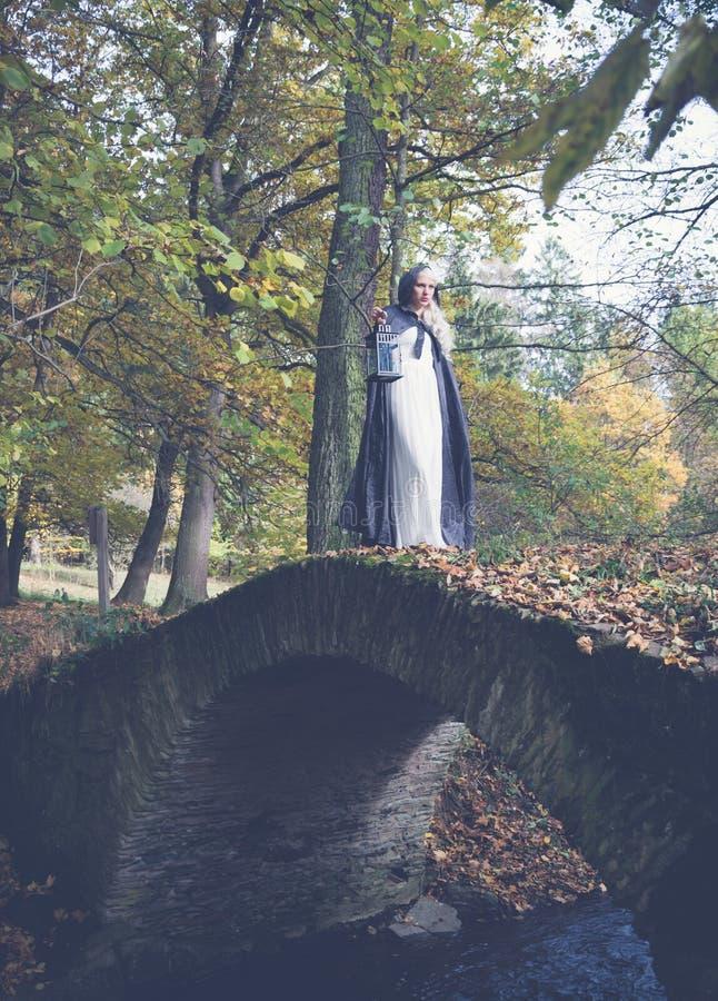 Vrouw in witte kleding op een steenbrug stock foto