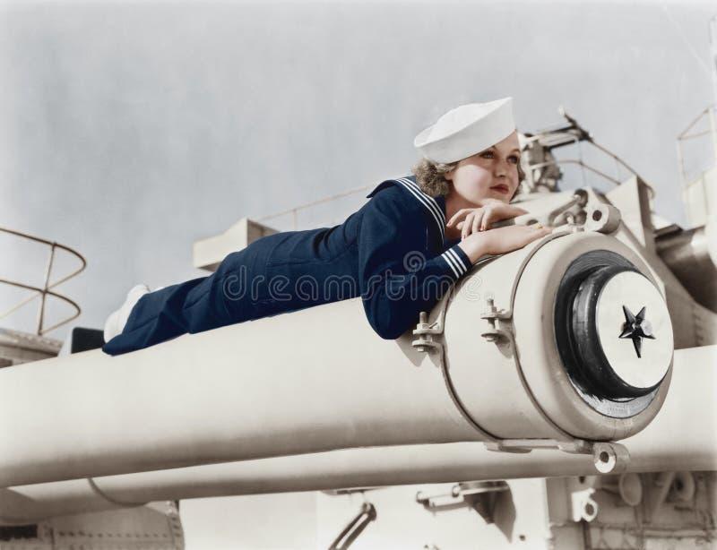 Vrouw in zeelieden het eenvormige liggen op een kanon (Alle afgeschilderde personen leven niet langer en geen landgoed bestaat Le stock foto's