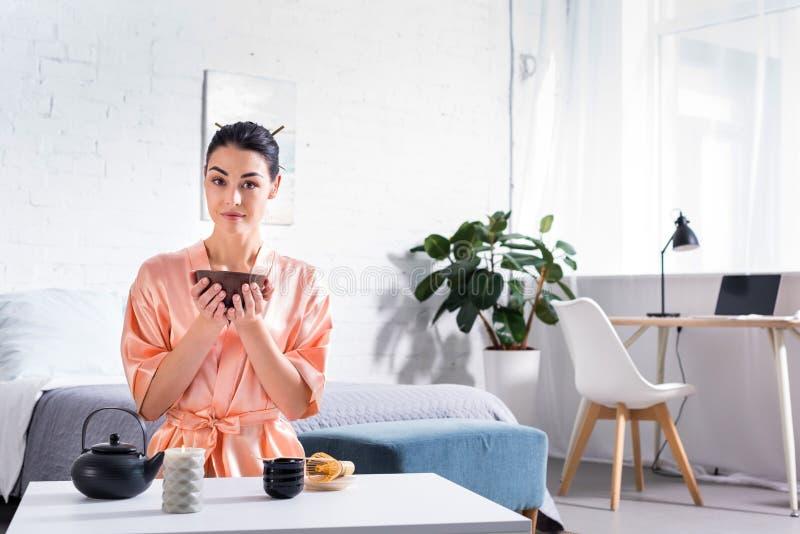 vrouw in zijdebadjas met houten kom in handen die theeceremonie in ochtend hebben royalty-vrije stock fotografie