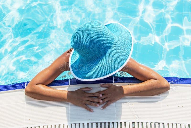 Vrouw in zonhoed in een zwembad Hoogste mening stock afbeelding