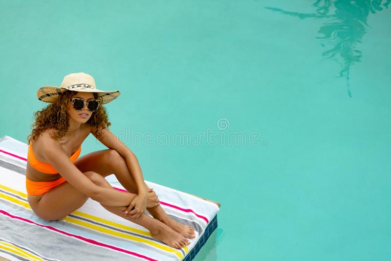 Vrouw in zonnebril en hoedenzitting bij de rand van zwembad royalty-vrije stock foto