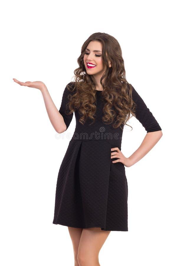 Vrouw in Zwart Mini Dress Presenting Something royalty-vrije stock fotografie