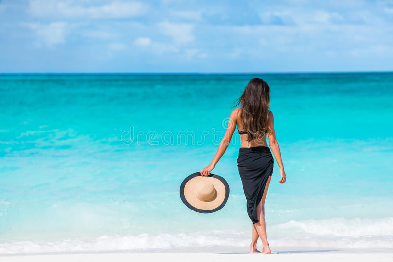 Vrouw in zwarte bikini en sarongen die zich op strand bevinden royalty-vrije stock afbeelding