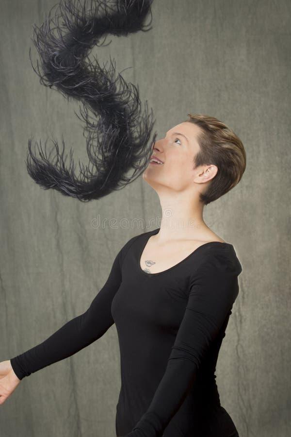 Vrouw in zwarte kleding met een boa in de studio stock fotografie