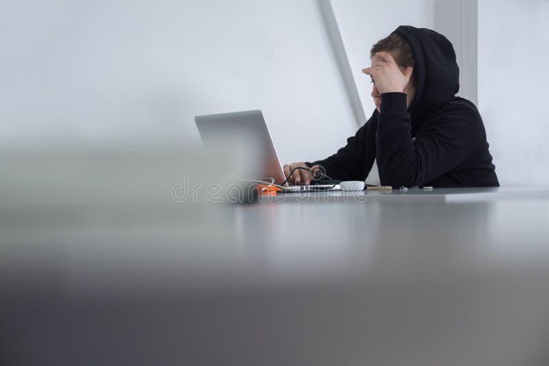 Vrouw in zwarte kleding met laptop Wijfje in kapzitting bij lijst De zitting van de student met laptop Student in hijab royalty-vrije stock afbeelding