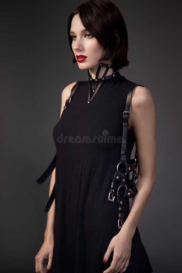 Vrouw in zwarte kleding met leertoebehoren stock afbeeldingen