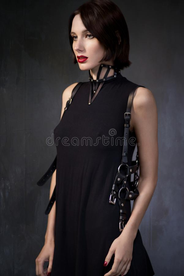 Vrouw in zwarte kleding met leertoebehoren royalty-vrije stock afbeeldingen