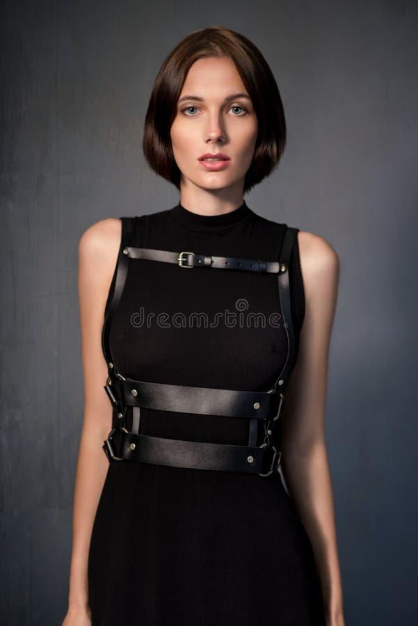 Vrouw in zwarte kleding met leertoebehoren stock foto