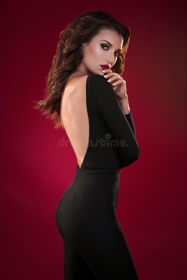 Vrouw in zwarte kleding op de rode achtergrond stock afbeelding