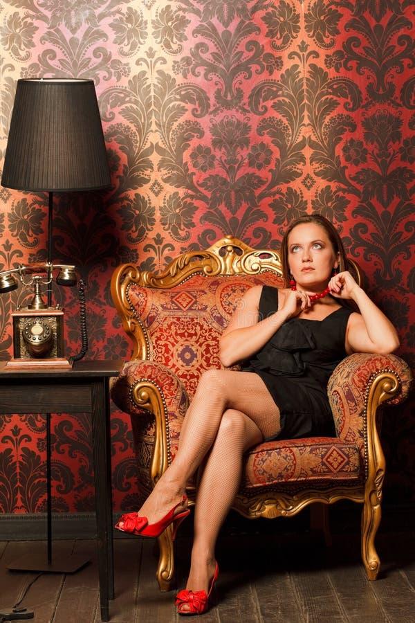 Vrouw in zwarte kledingszitting op uitstekende stoel royalty-vrije stock afbeelding