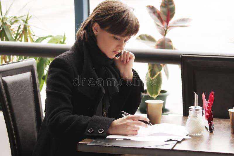 Vrouw in zwarte laag die in koffie werkt royalty-vrije stock foto