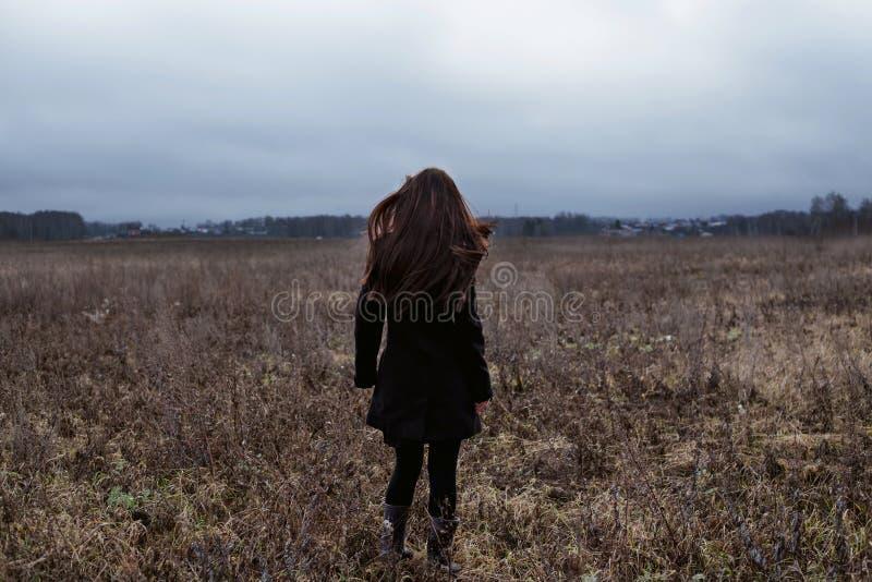 Vrouw in zwarte laag die zich op koud de herfstgebied bevinden royalty-vrije stock foto