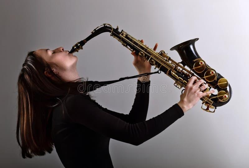 Vrouw in zwarte met saxofoon stock afbeelding