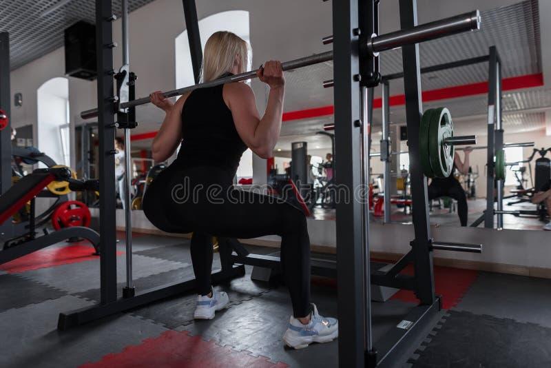 Vrouw in zwarte modieuze sportkleding in tennisschoenen crouches met een metaalgier op schouders binnen Meisje die sterkteoefenin royalty-vrije stock afbeelding