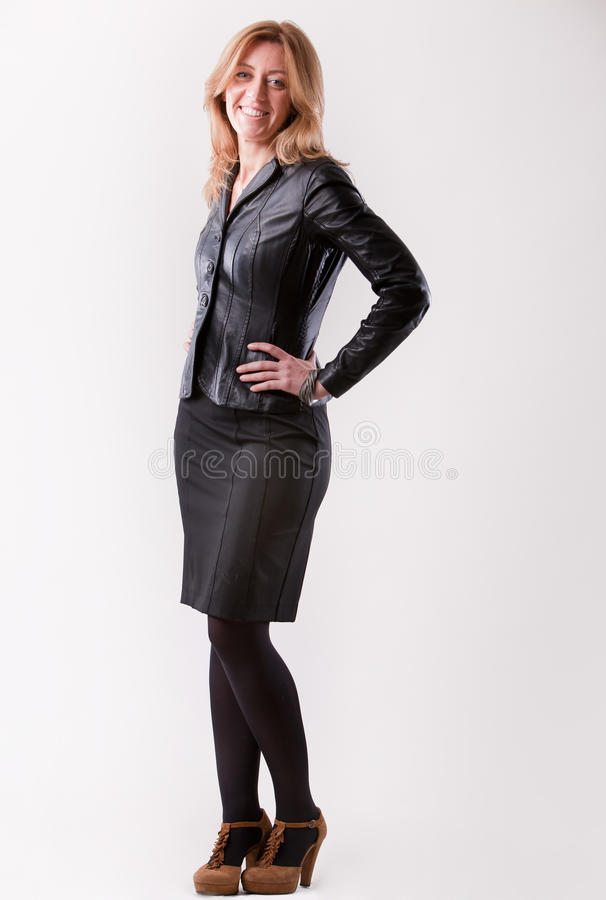 Vrouw in zwarte status en het glimlachen stock afbeeldingen