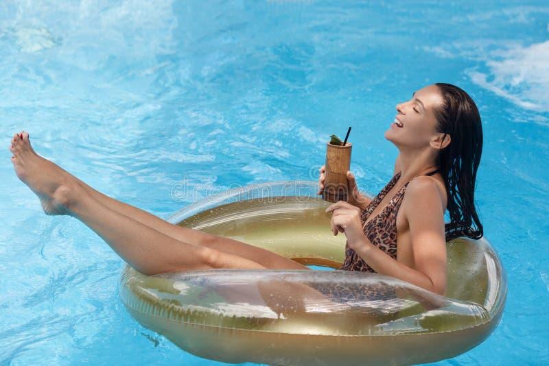 Vrouw in zwembad op rubberring die terwijl het hebben van vakantie, genietend van zomer, bestedend tijd vers drinken ontspannen stock foto's