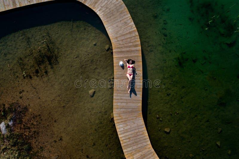 Vrouw in zwempak die op de pijler zonnebaden stock foto