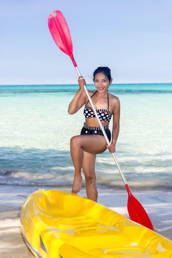 Vrouw in zwempak die zich op het strand met peddel bevinden stock foto's