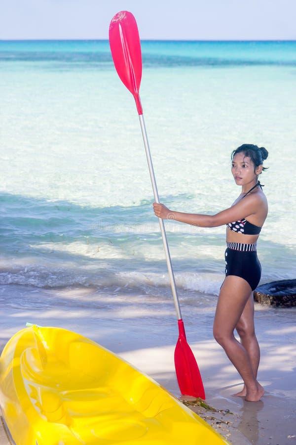 Vrouw in zwempak die zich op het strand met peddel bevinden stock afbeeldingen