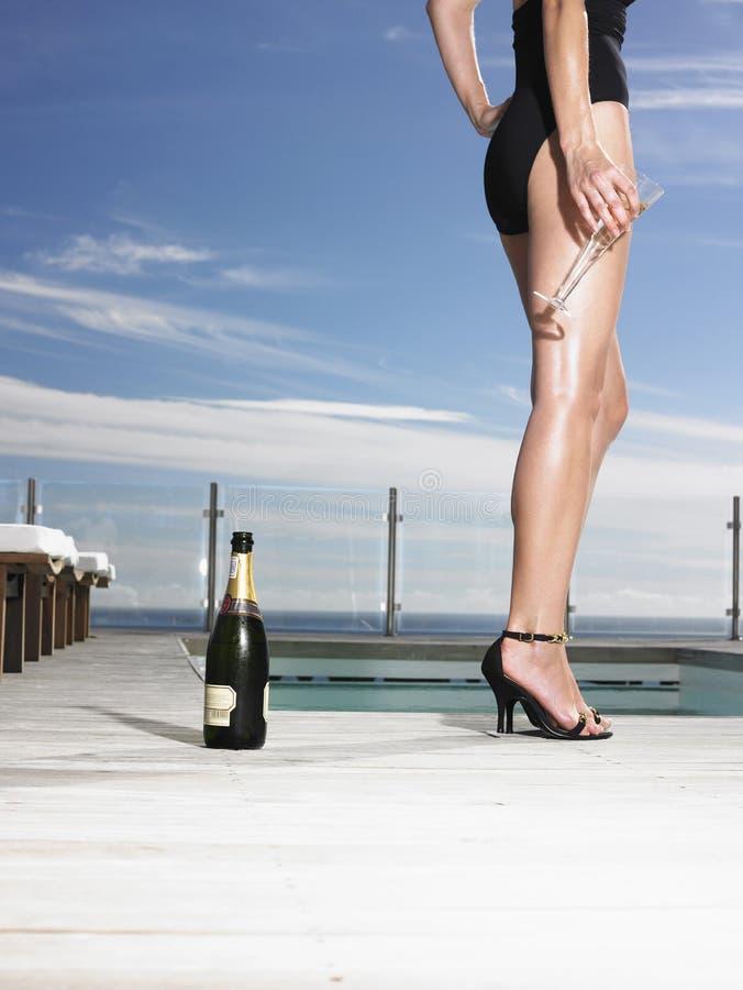 Vrouw in Zwempak met Champagne By Pool stock afbeelding