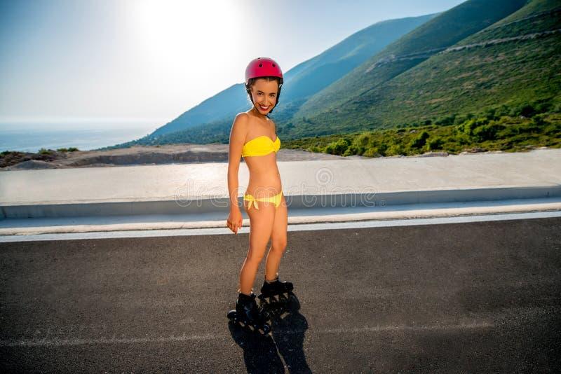 Vrouw in zwempak met rollen op de weg stock foto's
