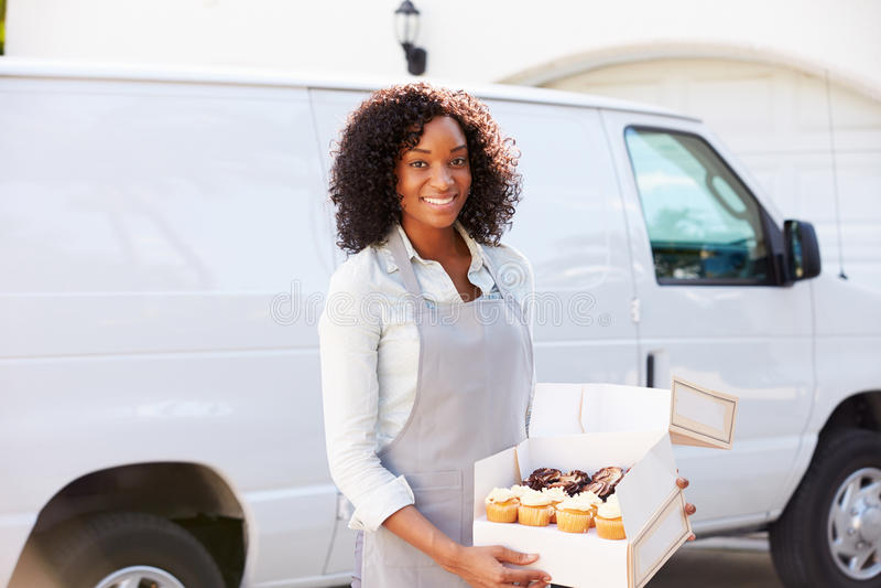 Vrouwelijk Baker Delivering Cakes Standing in Front Of Van stock foto