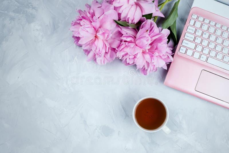 Vrouwelijk bedrijfsmodel met roze laptop, pioenenboeket en kop van warme thee royalty-vrije stock afbeeldingen