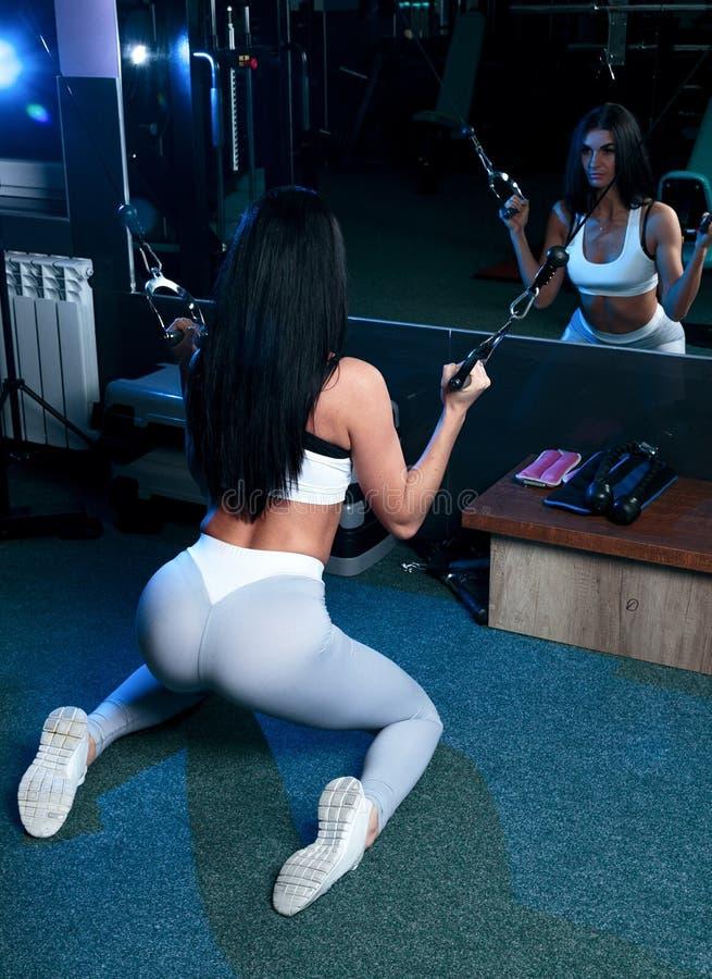 Vrouwelijk brunette in sexy beenkappen en korte t-shirt, die exerci doen stock foto