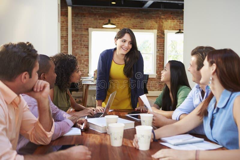 Vrouwelijk Chef- Addressing Office Workers op Vergadering stock afbeelding