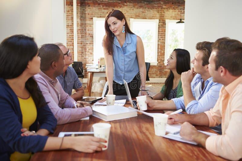 Vrouwelijk Chef- Addressing Office Workers op Vergadering stock afbeeldingen