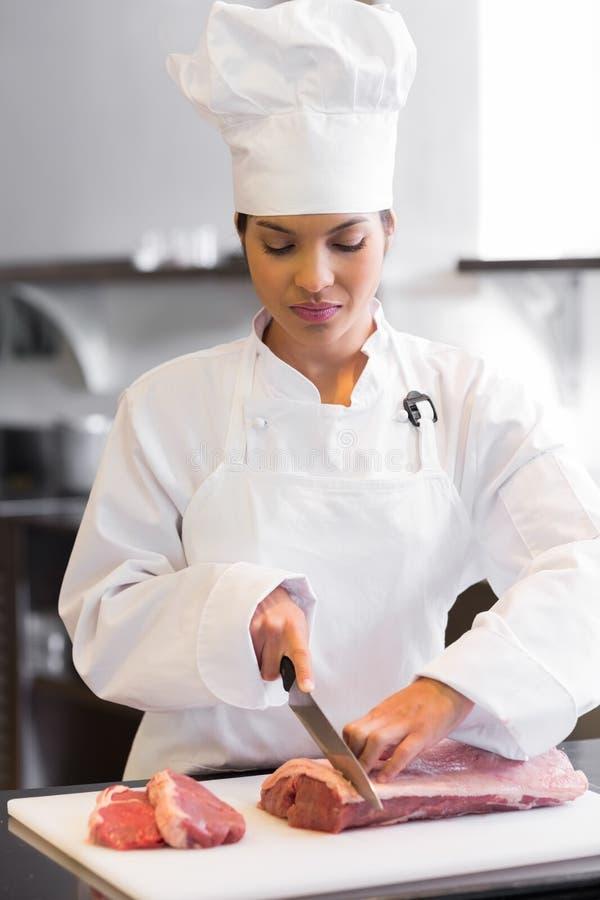 Vrouwelijk chef-kok scherp vlees in keuken royalty-vrije stock foto's