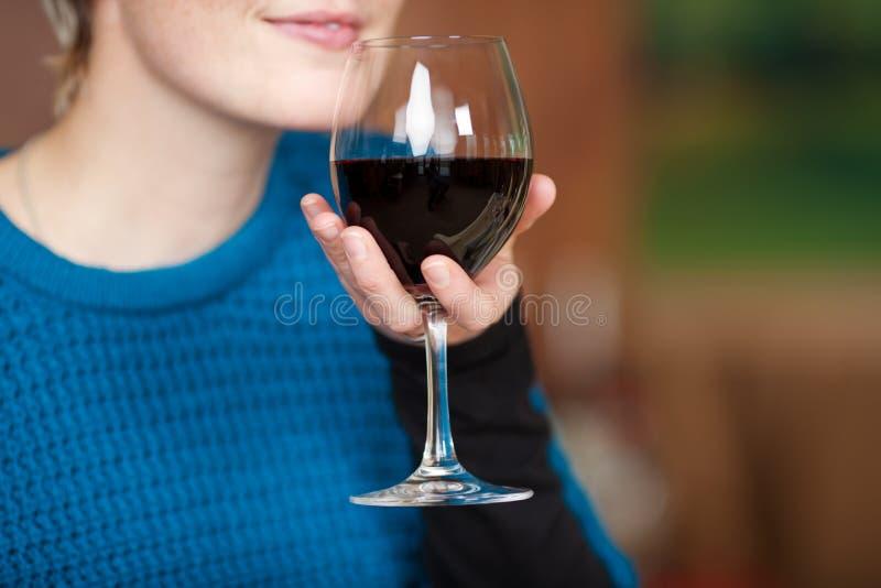 Vrouwelijk de Rode Wijnglas van de Klantenholding bij Restaurant royalty-vrije stock afbeelding