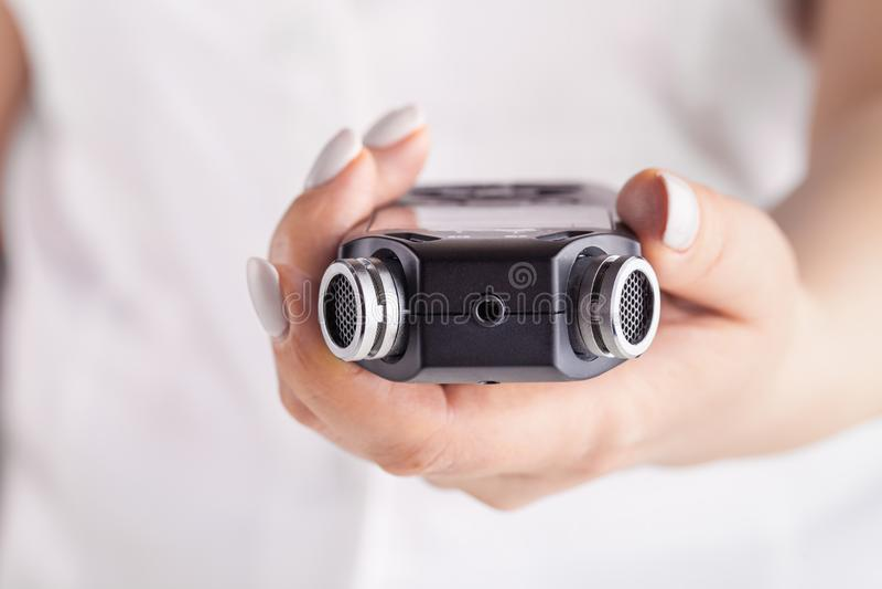 Vrouwelijk de stem audioregistreertoestel die van de handholding voor het documenteren van geluid gebruiken royalty-vrije stock fotografie