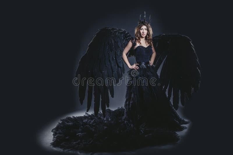 Vrouwelijk demon met zwart vleugelskostuum in Carnaval en godsdienstig royalty-vrije stock afbeelding
