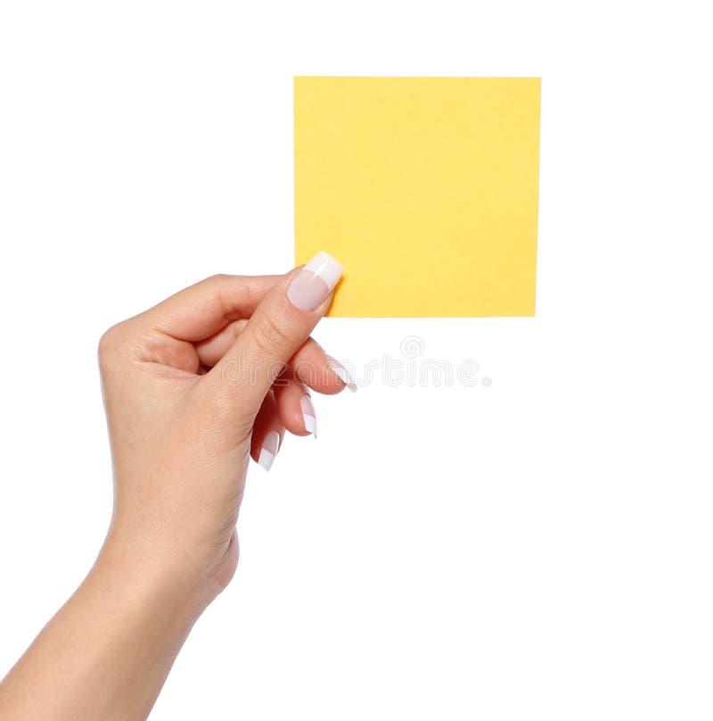 Vrouwelijk die de notadocument van de handholding, op witte, gele sticker wordt geïsoleerd= stock foto