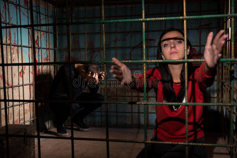 Vrouwelijk die slachtoffer in een metaalkooi wordt gevangengenomen die handen door bereiken stock afbeeldingen